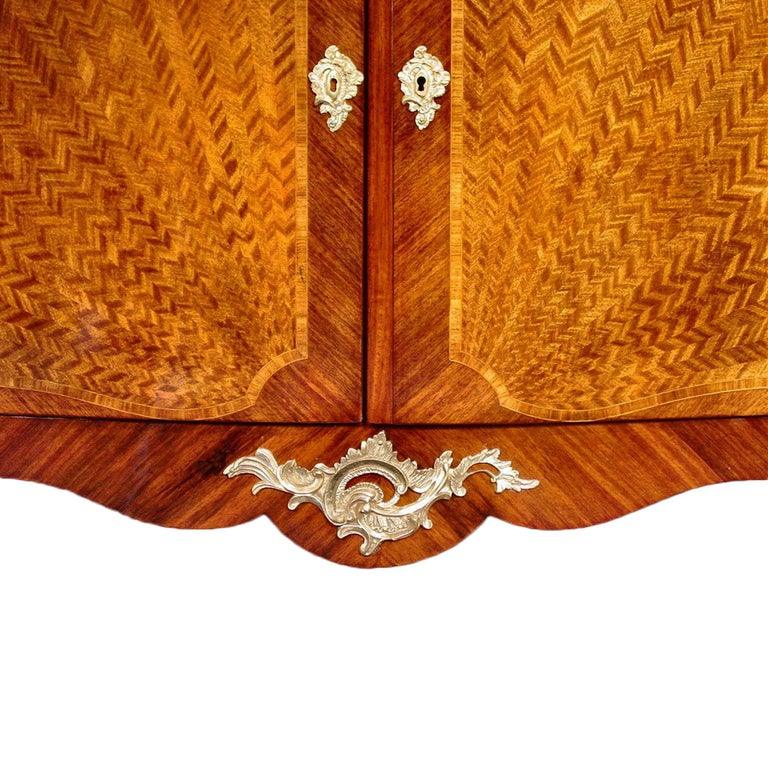 A handsome two-door French late 19th century Louis XV st. cabinet. The cabinet is raised by cabriole legs below an elegant scalloped apron. Above are two doors with an elaborate inlay of tulipwood quarter sunburst marquetry bordered by Kingwood.