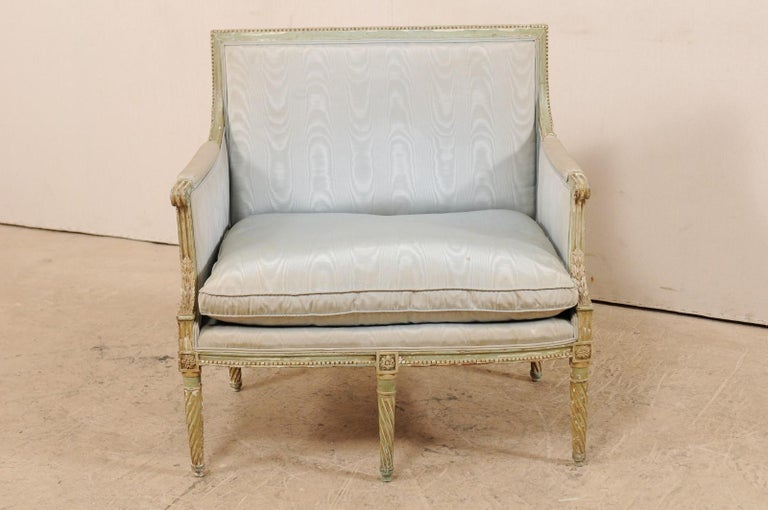 A French Louis XVI style marquise wide seat chair from the late 19th century. This antique Louis XVI style chair from France, with its original paint, features a straight crest rail along the back with carved bead trim, upholstered manchette arms,