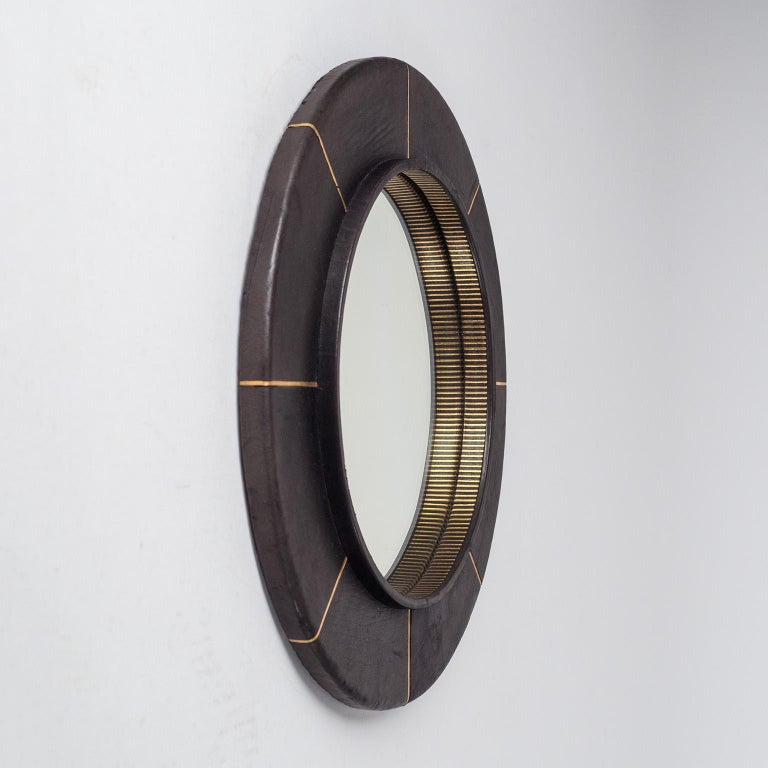 French leather-clad mirror, circa 1980, with gold-embossed decorations. Black anilin leather with radial gold lines embossed into the leather. Good condition with minor wear to the leather and some clouding on the mirror. Reflective area is