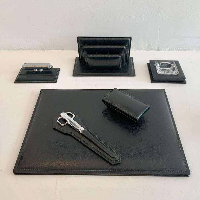 Fantastic 6-piece French leather desk set by Le Tanneur. All pieces wrapped in dark green leather. Desk set includes: desk pad, ink blotter, mail holder, ashtray, adjustable calendar, chrome scissors and letter opener. Good vintage condition. Super