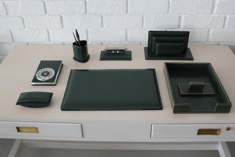 Full French leather desk set in the style of Jacques Adnet. Dark hunger green leather set includes seven pieces - including paper tray, envelope mail holder, calendar, blotter, pen holder and old fashioned rotary telephone book! Excellent vintage