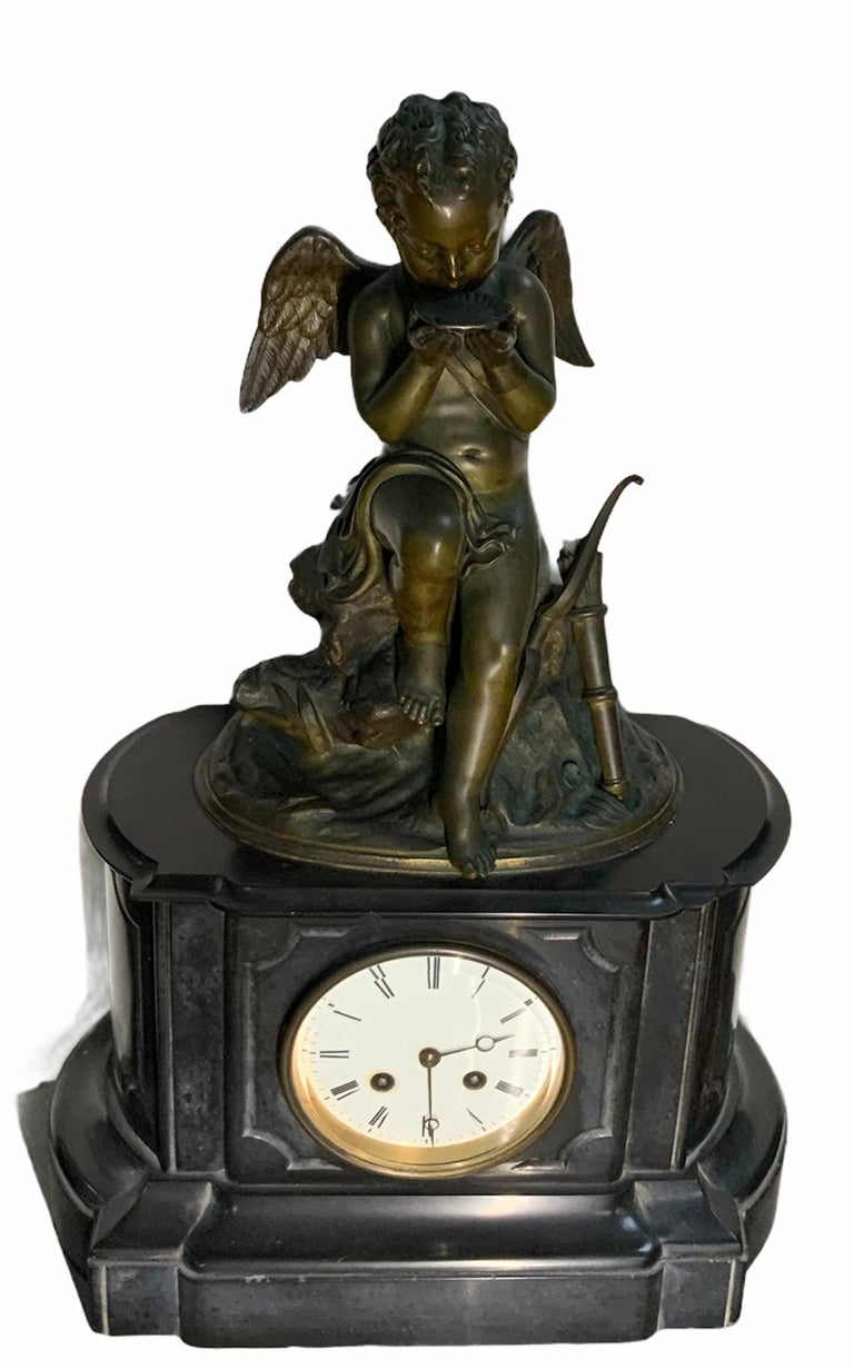 This is a French figural patinated bronze sculpture mantel clock of a winged Cherub hunter by Lemire Charles Gabriel Sauvage. The thirsty Cherub is seated over a large rock with some foliages drinking water from a seashell. He is semi nude and a
