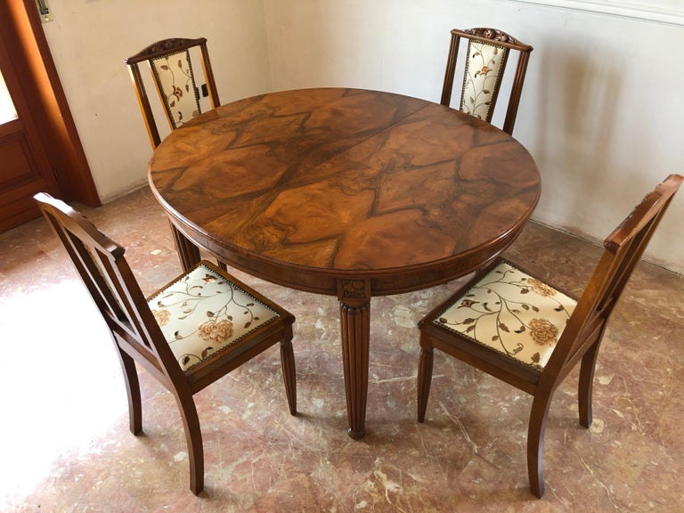French liberty Art Nouveau dining set composed by a dining table in a very valuable walnut feather, grooved legs with naturalistic motif, characteristic elements of the period and six beautiful chairs with decorative inlays on the backs, grooved