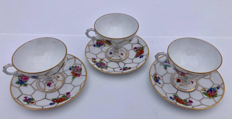 This is a set of three lovely French Limoges bone china tea cups with pedestal bottom and matching saucers. They have a gorgeous floral design with a honeycomb white background and gold accents. Sizes: Saucers: W 4.25 x H 0.5 Cups: W (with