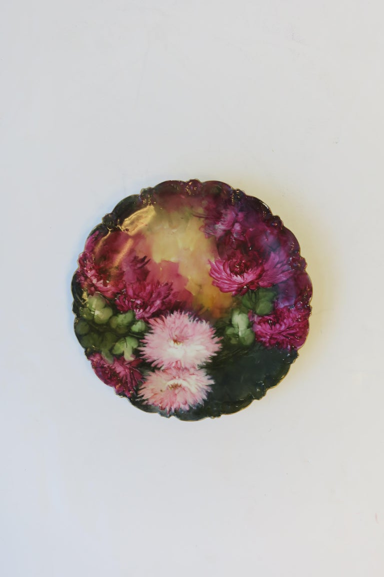 An early-20th century French hand-painted plate by T & V, Limoges, France. Plates' design is beautiful fuchsia-purple and pink mum flowers and green leaves, finished with a gold gilt scalloped edge. Maker's mark on bottom as show in image #7. Plate