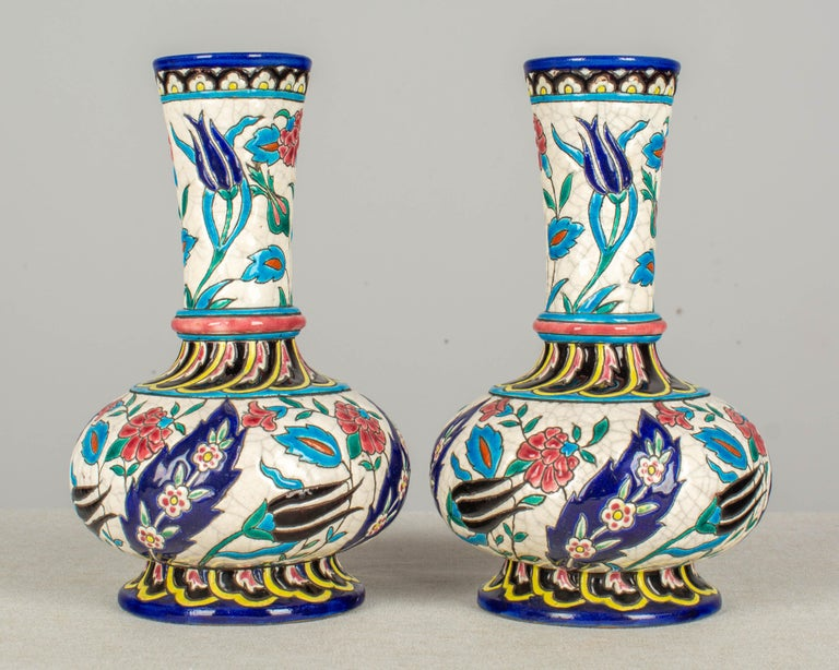 A pair of late 19th century French Longwy enamel cloisonné ceramic bottle form vases. Decorated with hand painted stylized floral and leaf motifs in shades of indigo blue, turquoise, black, rose, green, and yellow on a white crackle ground.