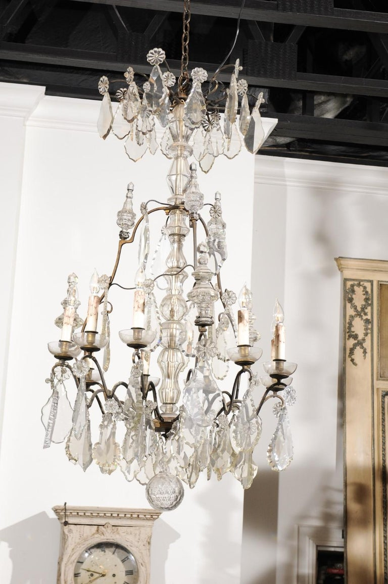 A French nine-light crystal chandelier from the mid-19th century, with iron armature. Born in France during the reign of King Louis-Philippe, this exquisite chandelier features a central crystal column, surrounded by a ring of pendeloques and