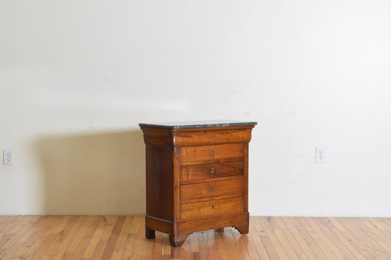 Having a marble top with rounded front edges above a conforming case housing 5 drawers, the top drawer hidden, raised on bracket feet.
