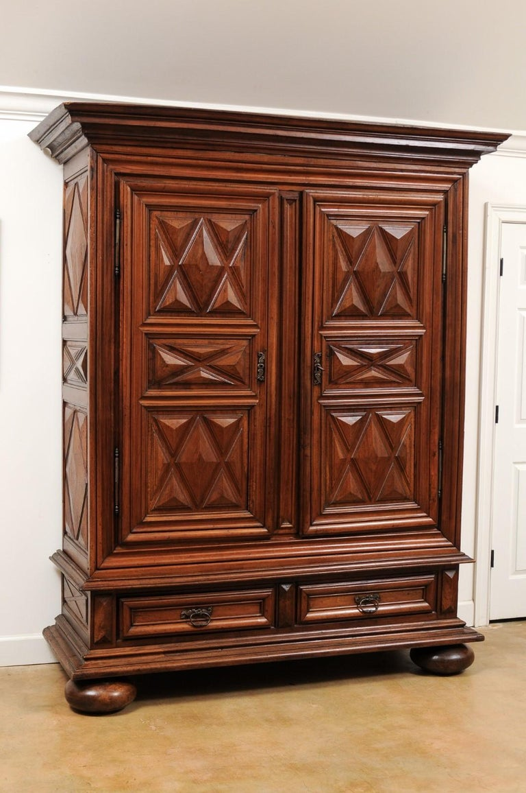 A French Louis XIII style walnut armoire from the 19th century, with raised diamond motifs, doors and drawers. Born in France during the 19th century, this stunning walnut armoire features a molded cornice overhanging a geometric front adorned with