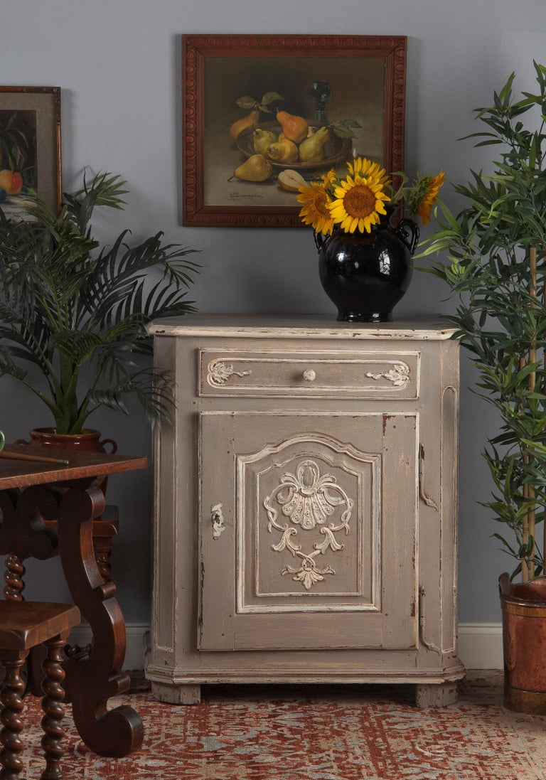 A charming oak painted Louis XIV confiturier or preserves cabinet, French 18th century. Distressed light gray paint with cream highlighting the decorative details. Paneled sides and canted front corners, a single drawer on top with a single door