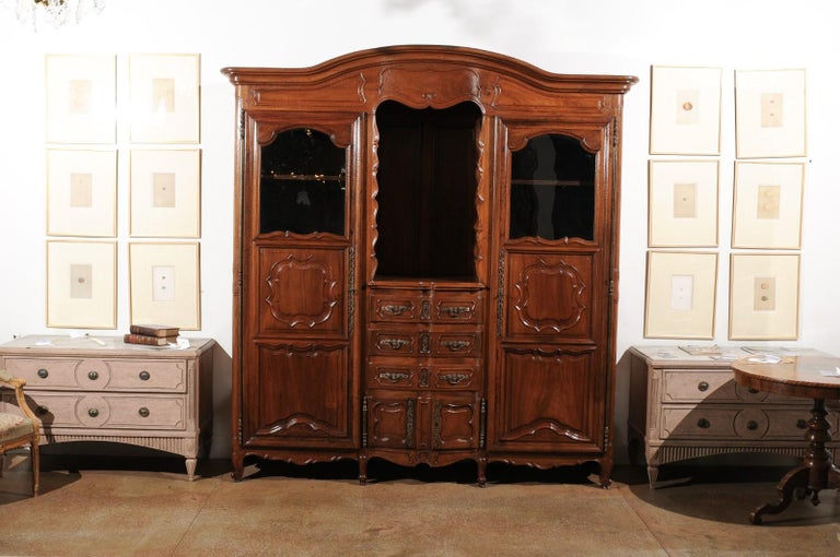 A French walnut Louis XV period Provençal bookcase from the 18th century, with bonnet top, two doors and three drawers. Born in Provence during the 18th century, this stunning walnut bookcase features a