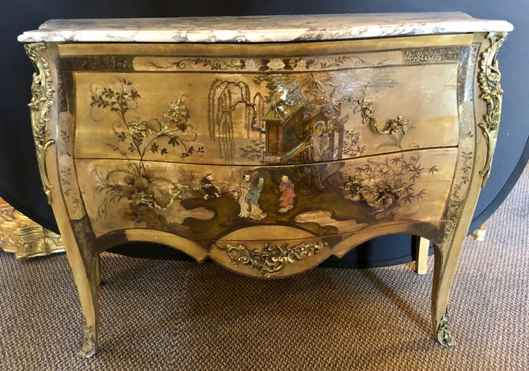 French Louis XV chinoiserie Commode. Having a Bombe form and white with gray and black veined marble top this finely crafted commode or dresser is simply stunning. The case with finely painted raised carved figures of men and woman with their