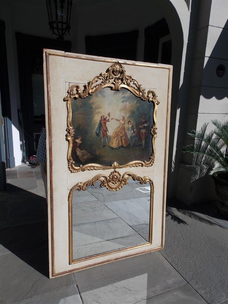 French Louis XV gilt and painted trumeau mirror with a figural landscape painting, embellished shells, foliate scrolls, and retains the original shaped mirror with surrounding gilt foliage. The mirror retains the original paneled wood backing as