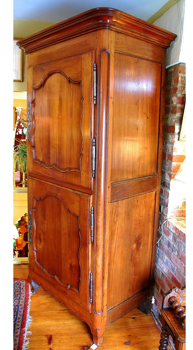 French Louis XV Period cherry and chestnut two-door bonnetiere with original steel hinges and locks, pegged construction. The beautifully carved paneled doors and deep cove molded cornice, along with the cabriole legs make this a Classic piece. As