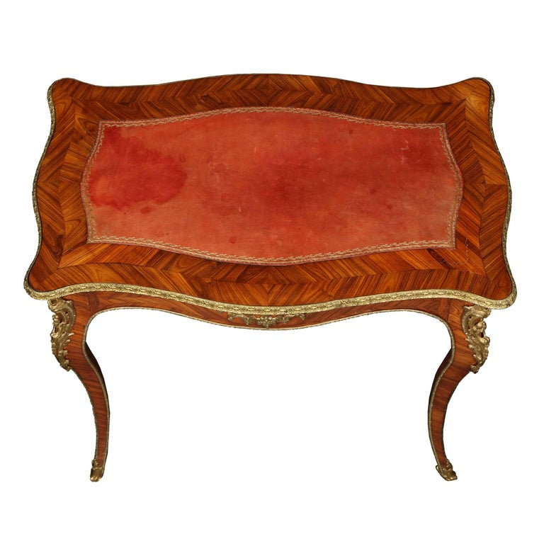 A very elegant French 19th century Louis XV st. tulipwood marquetry table with one drawer and a red leather top. The whole is elegantly ornamented with rich ormolu mounts on all sides and is all raised on high cabriole legs.