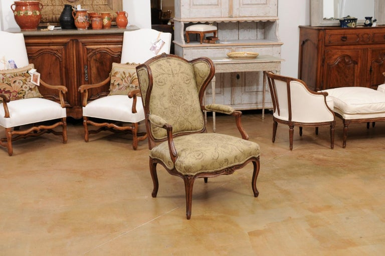 A French Louis XV style wingback chair from the late 19th century, with newer upholstery and carved floral motifs. Created in France during the last decade of the 19th century, this fauteuil features a wingback offering great privacy to the sitter,