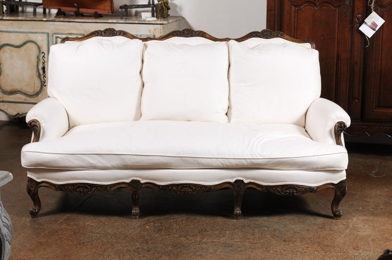 A French Louis XV style wooden three-seat sofa from the 19th century with cabriole legs and new upholstery. Born in France during the 19th century, this canapé presents the stylistic characteristics of the Louis XV era. The scrolled upper rail is
