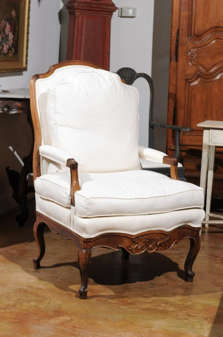 A French Louis XV style walnut armchair from the 19th century, with custom cushion, open arms and carved apron. Born in France during the politically dynamic 19th century, this walnut armchair features a slanted back with curved upper rail,