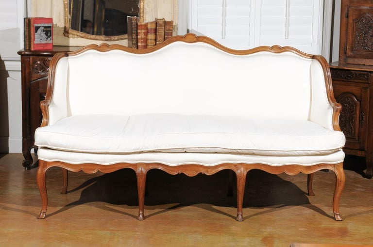 A French Louis XV style walnut sofa from the 19th century, with scrolled crest, cabriole legs and new upholstery. Born in France during the politically dynamic 19th century, this three-seat canapé features a straight back with scrolling upper rail,