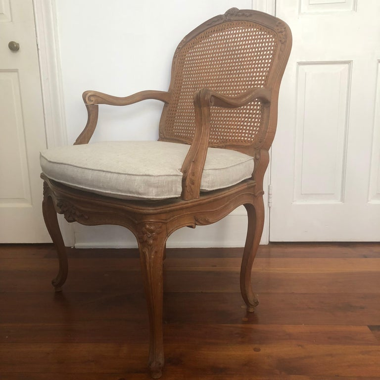 A fine Louis XV style Fauteuil in light walnut, nicely carved with acanthus leaves and flowers, with caned seat and back, on cabriole legs. The tailored cushion is recently upholstered in gray linen. The frame and the caning is very strong. Would