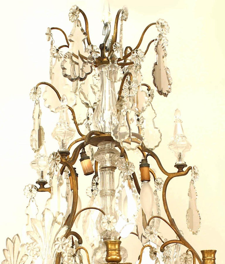 French Louis XV style bronze and crystal chandelier with various style crystal drops and finials and 8 candlestick holders and 8 light sockets. Missing 1 fan form crystal finial.