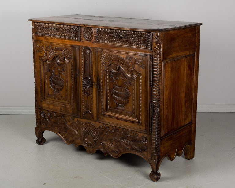 A late 18th century Louis XV style French buffet from Brittany made of solid walnut with exquisite finely detailed hand carved decoration. Raised panel doors have a pair of urns framed by an elaborately carved border. Deep apron with a central shell