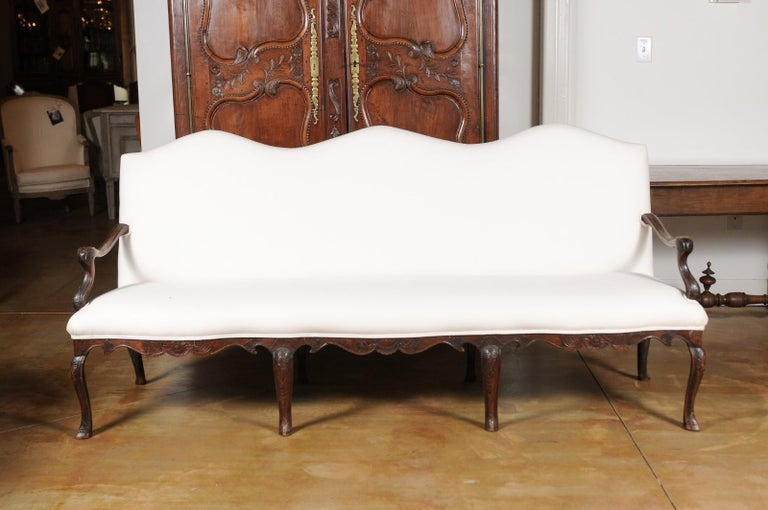 A French Louis XV style carved elm wood three-seat canapé from the 19th century, with cabriole legs and new upholstery. Born in France during the 19th century, this elm canapé features a slightly slanted tripartite camelback, resting above a