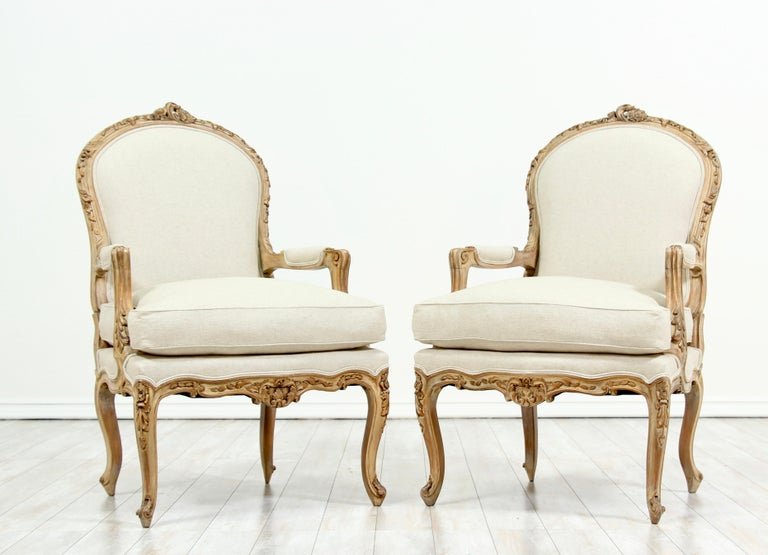 Beautiful, 1940s French Louis XV style carved fauteuils with new linen canvas upholstery. The chairs feature finely carved details and a soft cream wash finish. Loose seat cushions and self-welt details. The chairs are solid and sound, ready for