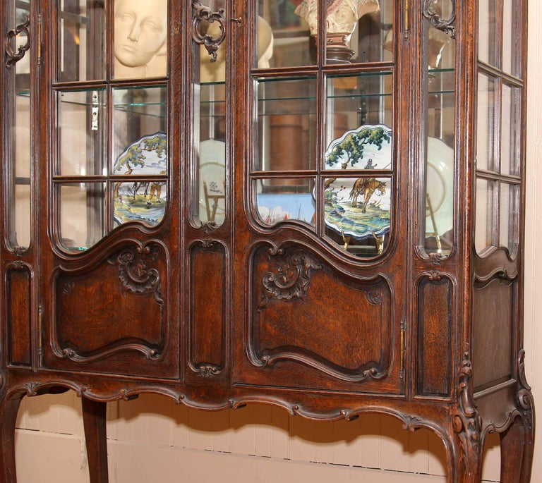 19th century French Louis XV style china cabinet. Carved solid quarter sawn oak. Interior fitted with light and plate glass shelving. Carved cabriole legs. An impressive 8