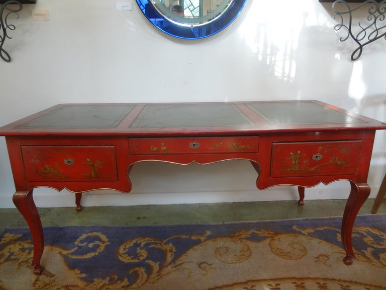 Outstanding French Louis XV style chinoiserie desk, writing table or bureau plat, circa. 1920. This large beautiful antique French desk is paint decorated on all sides in a lovely color of red with beautiful gilt accents resting on lovely sculpted