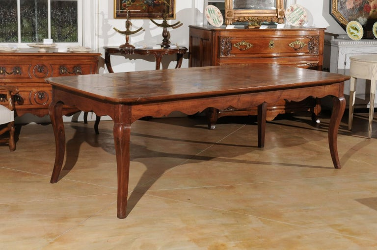 A custom made French Louis XV style dining table from Lyon made from 19th century parts, with parquetry top, carved apron and cabriole legs. Crafted in the Rhône Valley from 19th century wood, this Louis XV style dining table will comfortably seat 8