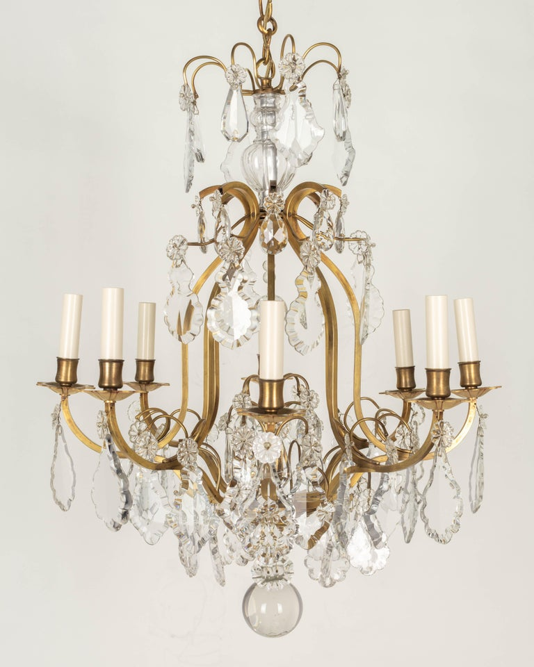 A Louis XV style French eight-light crystal chandelier with polished brass frame and a variety of prisms and rosettes. Original hollow glass column at the top, a large crystal ball, decorative chain and brass canopy. All the crystals are original,