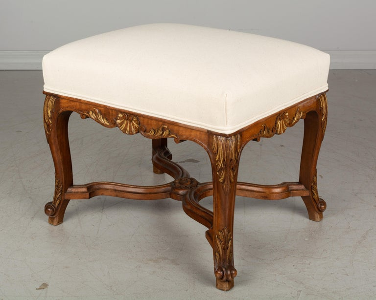 An early 20th century French Regency style foot stool or bench made of walnut with X-form stretcher. Beautiful hand carved shell motif and acanthus leaves, accented with gold leaf. Upholstered in neutral cotton canvas. Please refer to photos for
