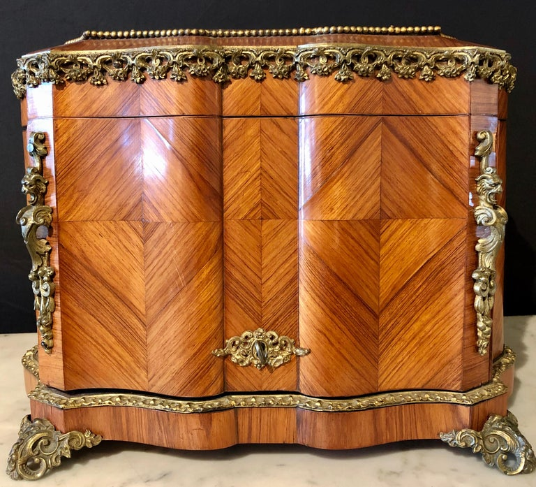 French Louis XV style gilt metal mounted Tantalus / bar. An almost perfect 19th century Tantalus set having a satin wood inlaid and bronze mounted box that fully opens to displace a removable carrying tray having four etched glass decanters, three