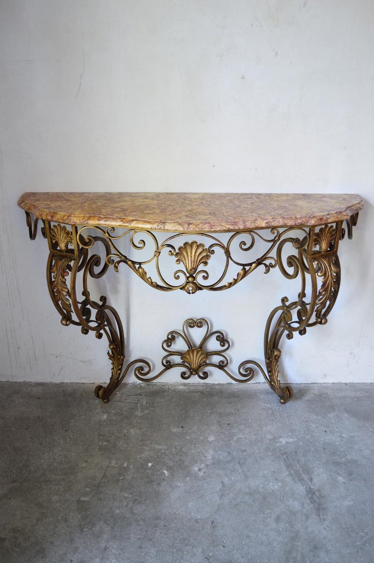 Superb wall console, wrought iron with golden patina. Beveled marble-top. In the 18th century French styles (Regence / Rocaille / Rococo / Louis XV), with characteristic motifs: acanthus leaves, shells, scrolls. France, 1930s. In excellent