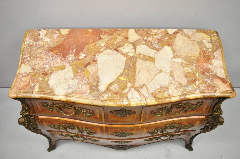 French Louis XV style inlaid marble-top bombe commode chest with bronze figures. Item features stunning marquetry inlay throughout, bronze hardware, bronze male and female faces, shaped rogue marble top with beveled edges, working lock and key, 5