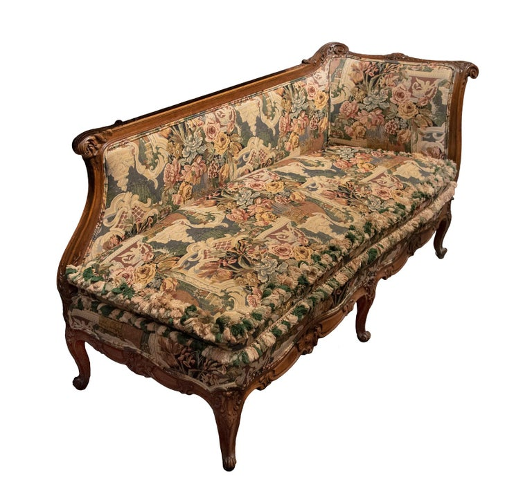 Crafted in France in the latter part of the 19th century in hand carved oak with floral and acanthus leaf motifs. Comfortably upholstered in an intricate floral tapestry material.  Measures: 36 H x 66 W x 26.5 D inches, 18.5 in. seat height.