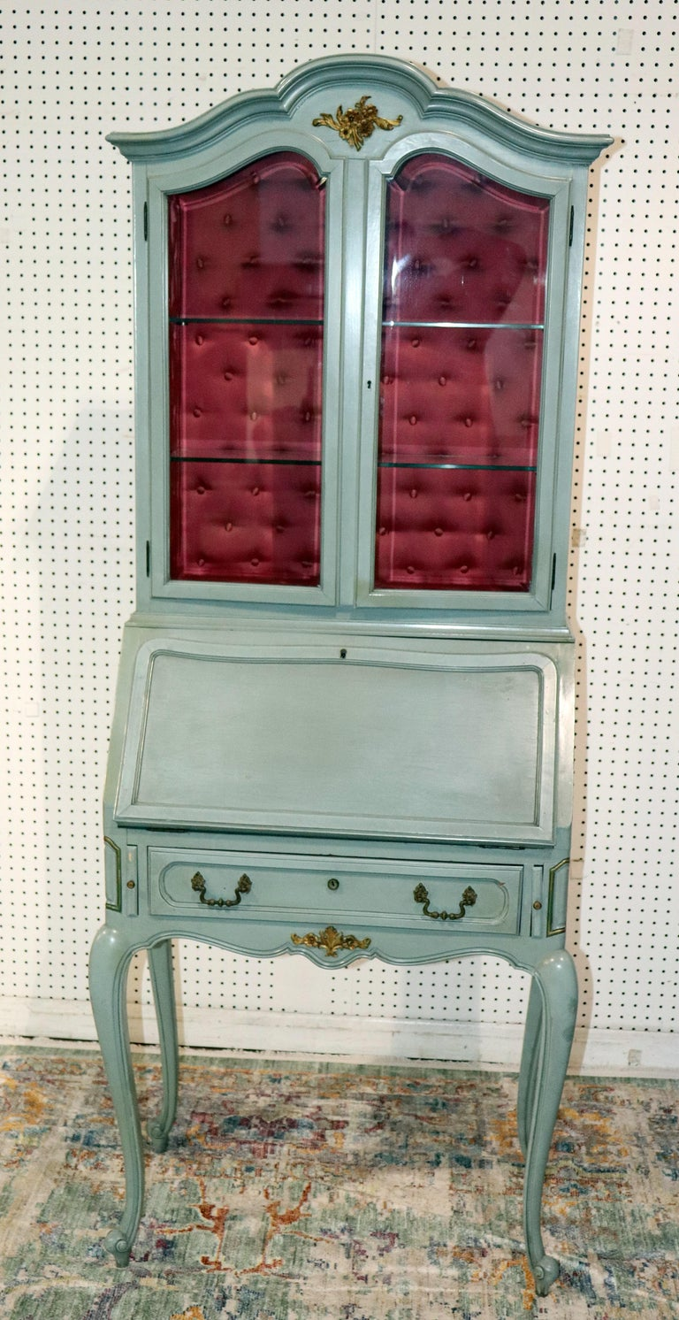French Louis XV style secretary desk or china cabinet with bronze hardware. The top has 2 doors with 2 glass shelves and a silk tufted interior. The bottom has a drop desk containing 2 drawers over 1 drawer. This is a very high quality and unique