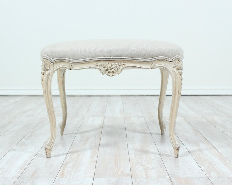 1920s French Louis XV-style carved wood tabouret or stool with new linen upholstery. Original paint finish is naturally distressed.