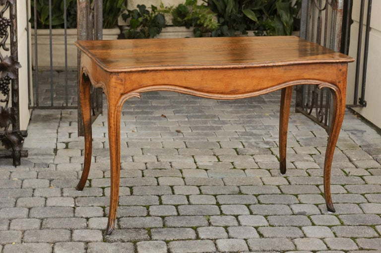A French Louis XV style walnut console table from the early 19th century, with cabriole legs. Born in France during the Restauration period that saw the temporary return of the Bourbon monarchy, this exquisite walnut console table presents the