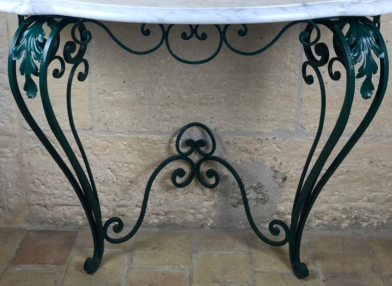 An elegantly formed Louis XV style wrought iron base and a serpentine shaped white Carrera marble top, circa 1950.  Good iron work and easy to fasten to the wall. Measures: 42 1/2