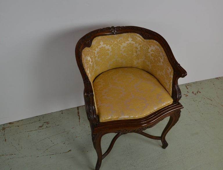 A French Louis XV hand carved vanity chair. Fine quality carvings of Acanthus leaf and medallions. Double crinoline stretcher with center carved medallion. Upholstered in a gold and beige damask fabric.