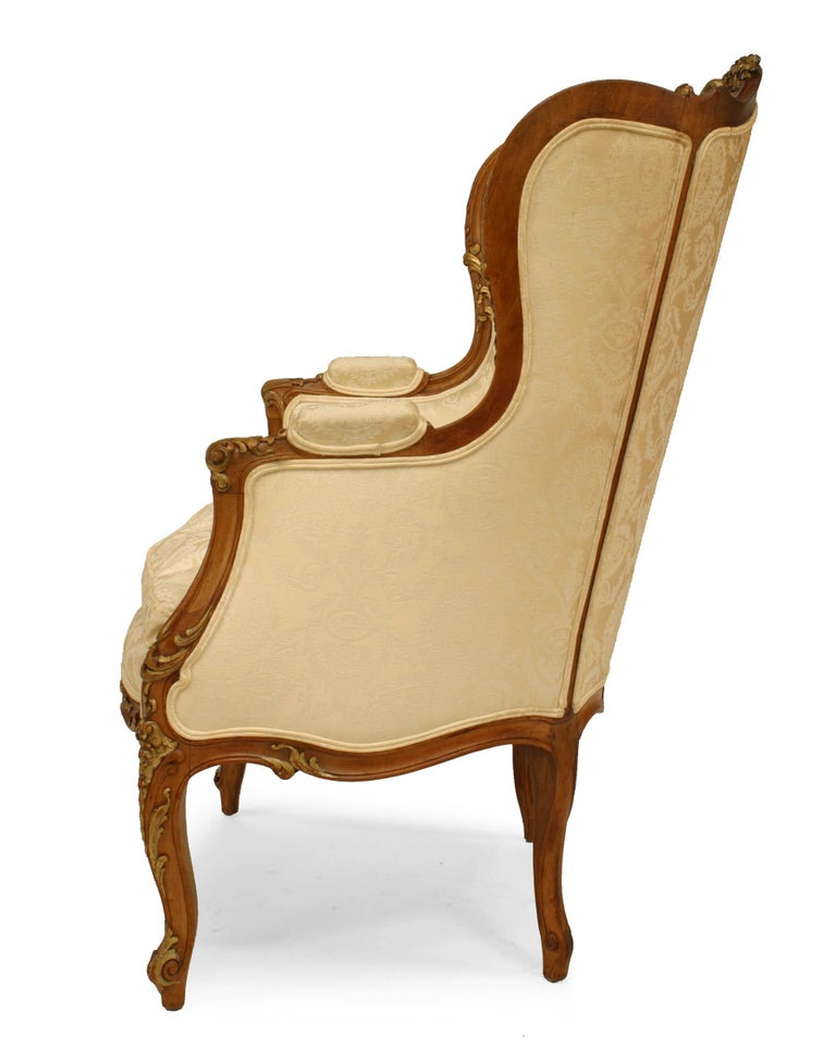 Late 19th early 20th century French Louis XV style walnut bergere arm chair with gilt trim, white upholstery, and wing back.
