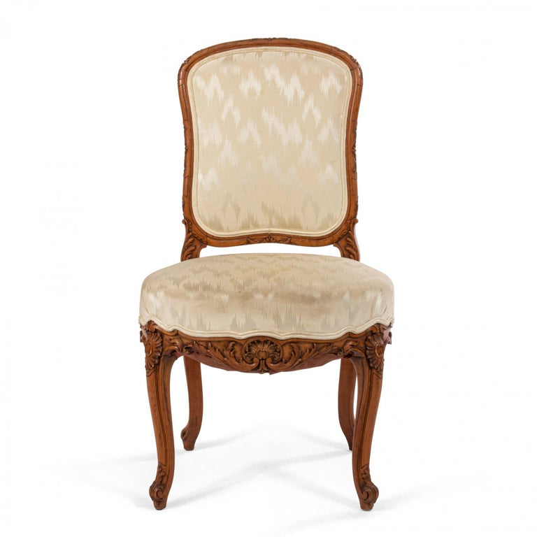 Pair of 19th century French Louis XV style walnut side chairs with a floral carved frame and upholstered seat and back.
