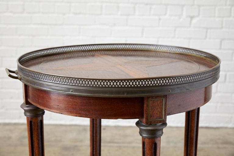 Exceptional French Louis XVI inlaid Bouillotte table or drink table. Features a bronzed galleried tray style top with handles on each side and a decorative pierced edge. The tabletop showcases the radiant mahogany grain with an inlay star motif