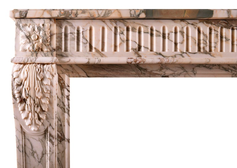 A fine quality French Louis XVI marble fireplace in striking Serravezza Breccia marble. The fluted frieze with carved square paterae to end blocks, the jambs with finely carved acanthus leaves and tapering panels below. Panelled outgrounds, late