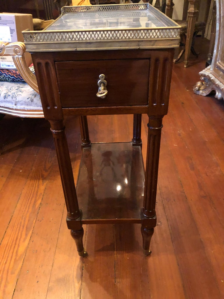 French Louis XVI mahogany occasional table with brass gallery and St Anne marble top. It has one drawer and original casters.