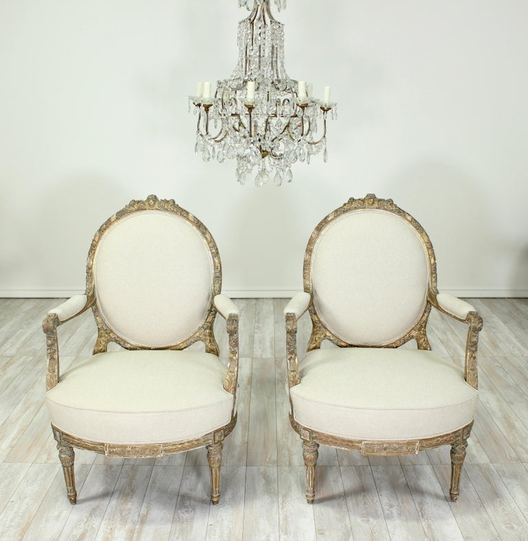 Exquisite, French 1920s pair of Louis XVI-style gilt wood bèrgeres with medallion shaped backrests and an intricately carved, delicate ribbon and floral motif. The original gilt finish has beautifully and naturally distressed over the decades to