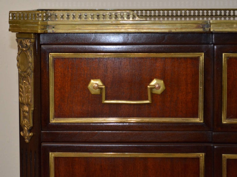A lovely three-drawer commode made of light and dark stained mahogany with brass mounts in the style of Maison Jansen's early 20th century work. Drawers feature brass trim, key escutcheons and Classic drop handles with hexagonal backplates. A white