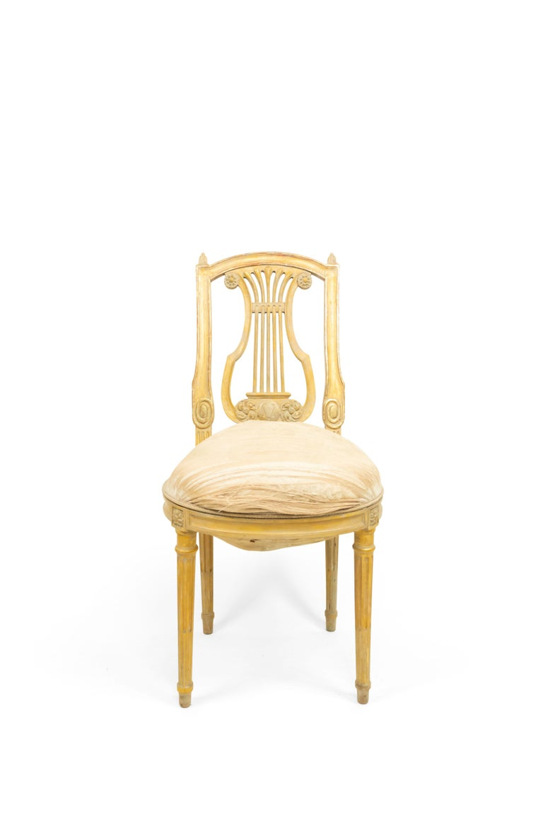Set of 6 French Louis XVI style (19th century) white and gilt lyre back side chairs with white damask upholstery.